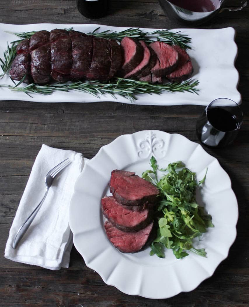 Overhead view of sliced beef tenderloin with rosemary on a plater and one plated serving.