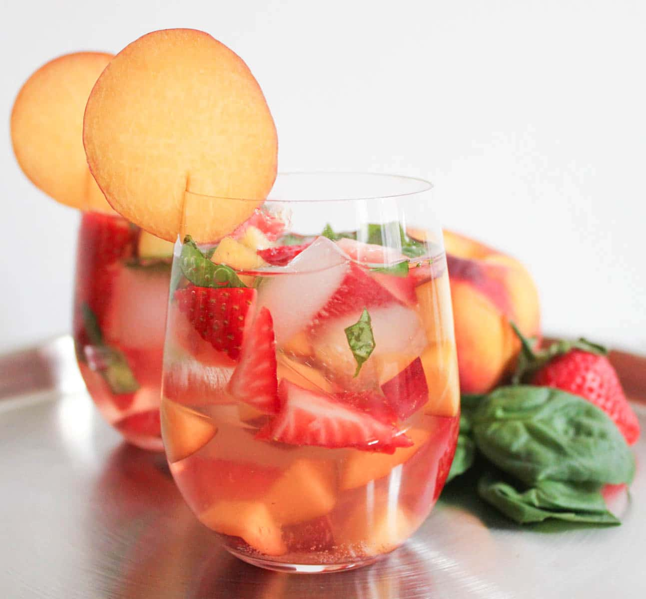 Two stemless wine glasses filled with sparkling rose sangria containing strawberries, peaches, and basil on a table displaying the fruits in their whole forms.