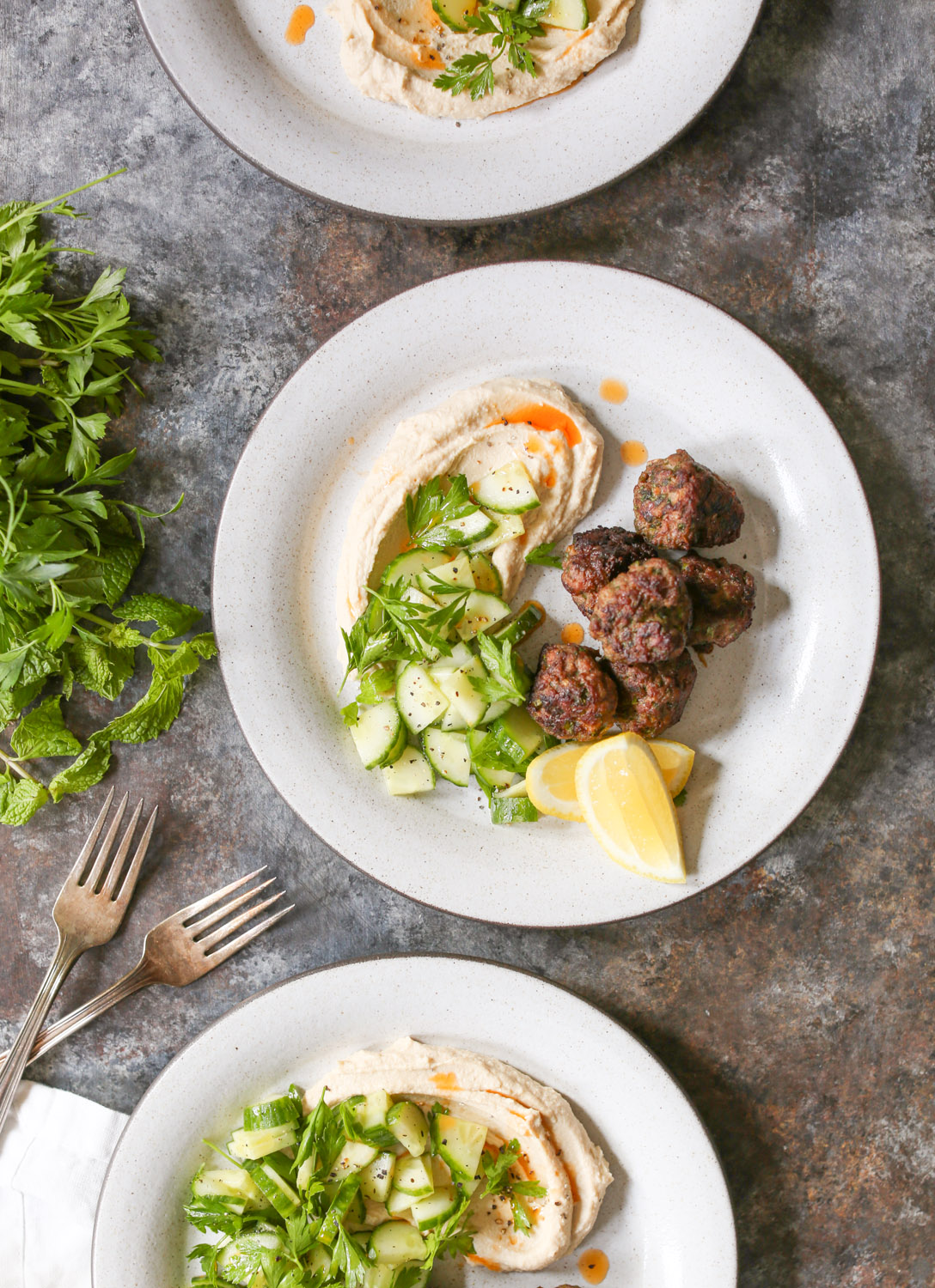 Overhead view of a plated serving of lamb kofta with hummus, cucumbers, and lemon wedges.