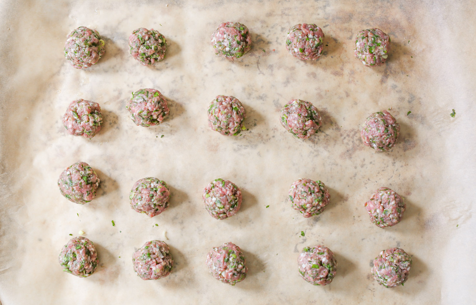Rolled spiced lamb meatballs on a parchment-lined baking sheet before going into the oven.