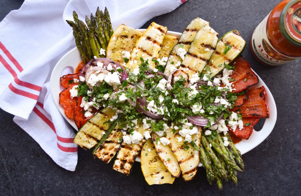Overhead view of a platter of grilled vegetables on top of a red and white dish cloth.